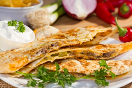rustic food: Southwest beef quesadila served with fresh chilli peppers and sourcream.
