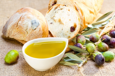 Ciabatta bread with olive oil and olive branch on burlap. Stock Photo
