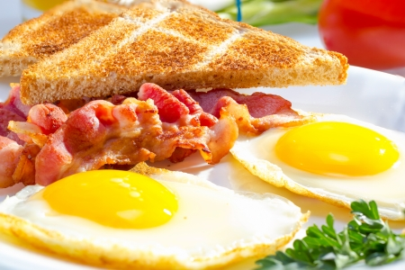 Bacon with sunny side up eggs served with toasts. Stock Photo