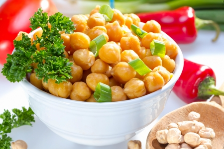 Cooked garbanzo beans (chick peas) in a bowl served with raw vegetables.
