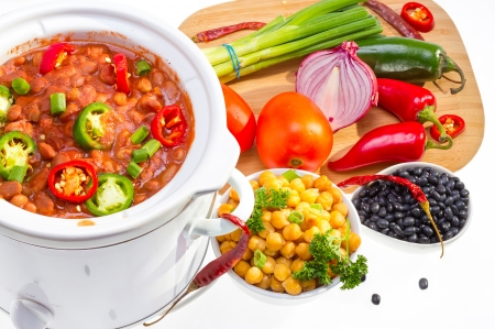 slow cooker: Pinto and garbanzo beans cooked in slow cooker with vegetables. Stock Photo