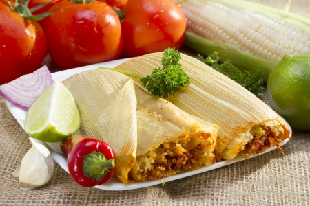 husk: Mexican tamale wrapped in corn husk served on plate.