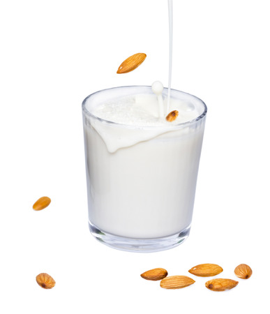Glass of almond milk with splash and spillage isolated on white background. Imagens