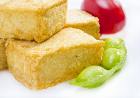 Fried tofu served with soy bean and tomato. Stock Photo