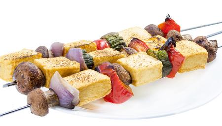 bean curd: Grilled tofu mushroom kebab on skewer served on plate.