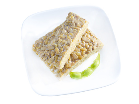 Yellow tempeh served on plate with edamame. Stock Photo