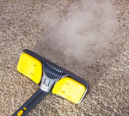 cleaning floor: Using dry steam cleaner to sanitize floor carpet. Stock Photo