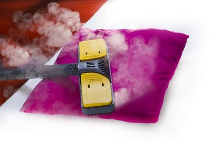 higienizar: Usando limpeza a vapor seco para higienizar travesseiro. Banco de Imagens