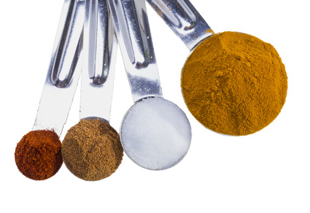 Spices in measuring spoons isolated on white background. photo
