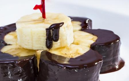 dipped: Dark chocolate dipped peeled banana, studio shot. Stock Photo