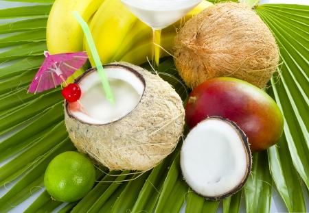 ヤシの葉にココナッツ ミルクとトロピカル カクテルを提供しています。