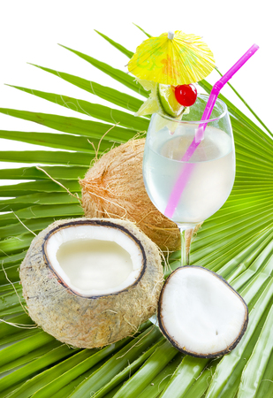 Coconut water in glass served on palm leaf .