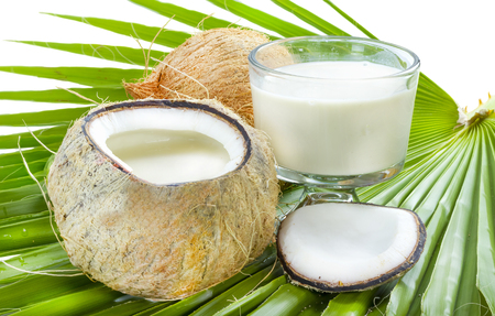 Open coconut with milk inside on palm leaf. Stock Photo