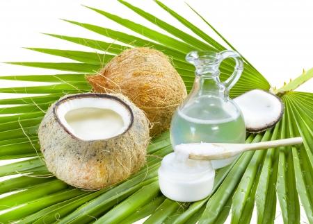 Huile de noix de coco liquide et solide sur feuille de palmier.