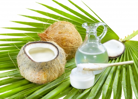 cooking oil: Liquid and solid coconut oil on palm leaf .