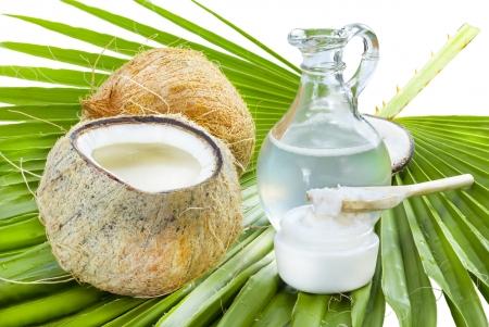 aceite de coco: El aceite de coco líquido y sólido en la hoja de palma. Foto de archivo