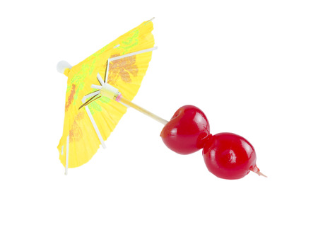 Cocktail cherry on party parasol isolated on white background.