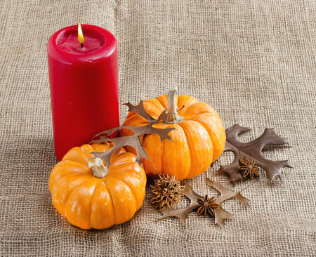 Orange mini pumpkins and red candle on brown burlap.