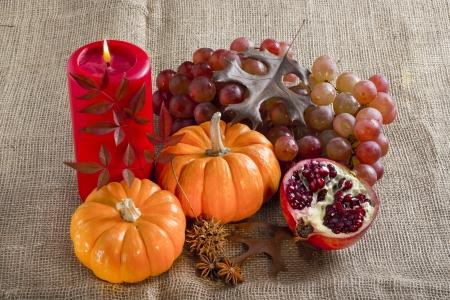 Orange mini pumpkins, grape and pomegranate on brown burlap .