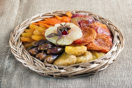 Dried fruits collection in braided basket on brown burlap . photo