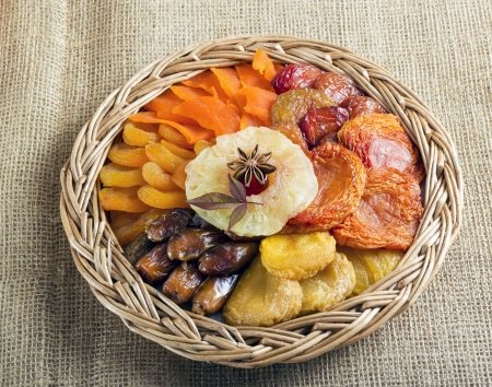 dry fruits: Dried fruits collection in braided basket on brown burlap . Stock Photo