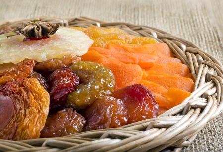 ciruela pasa: Frutos secos colección en cesta trenzada en la arpillera marrón.