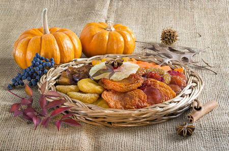 Dried fruits and mini pumpkins on brown burlap .