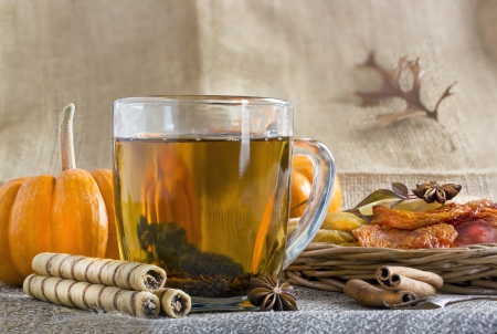 Glass cup of black tea with rolled wafers and dried fruits.