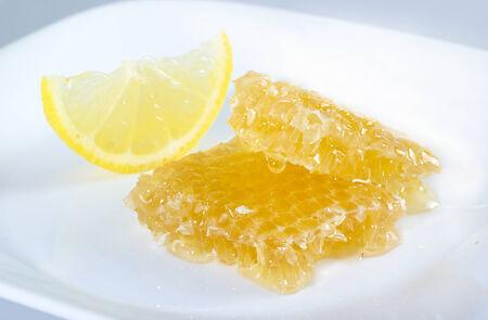 白い皿にレモンのスライスを蜂の巣の蜂蜜します。