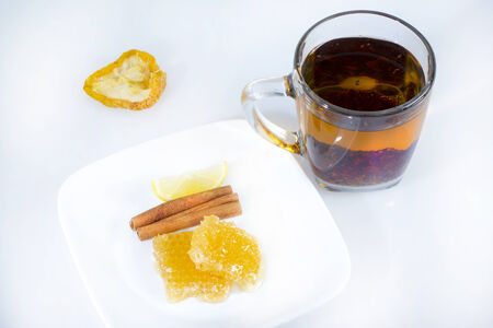 Black tea in glass cup with honeycomb and spices. Stock Photo