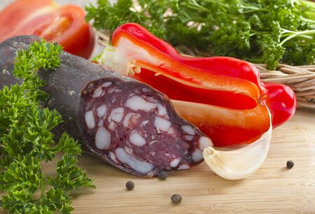 Sumer sausage with fat imcorpration served with vegetables.  Stock Photo