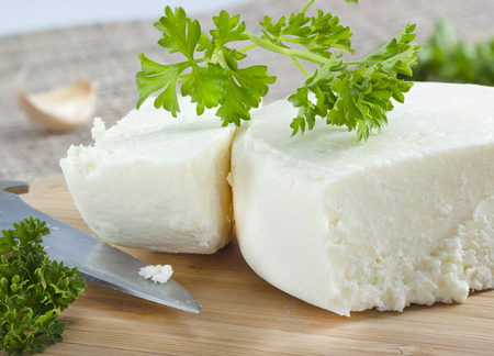 cheese knife: Cotija cheese with cilantro on cutting board . Stock Photo