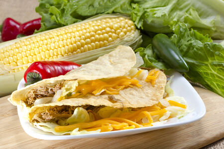 Hard shell carne asada (pulled pork) tacos served with corn Stock Photo