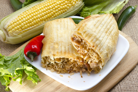 Pulled pork chimichanga served on plate with trimmed corn