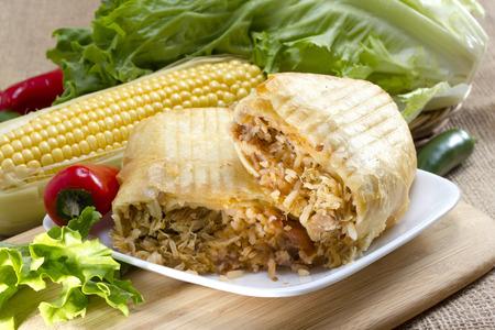 皿の上にトリミングされたトウモロコシ添え豚チミチャンガを引っ張った 写真素材