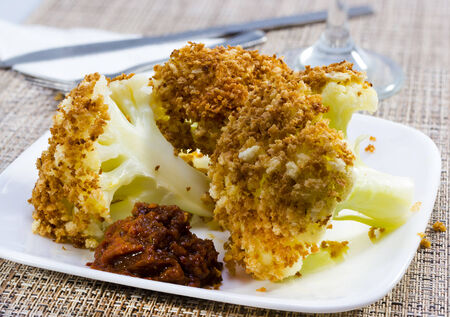 Fried breaded cauliflower served on plate .