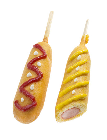 Corn dogs decorated with ketchup and mustard isolated on white background
