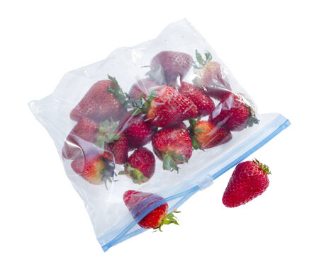 Strawberry in clear plastic bag isolated on white background .