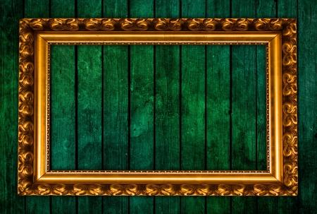 golden frame on green grunge wall