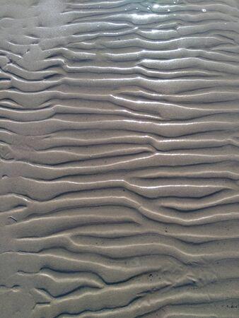 lignes ondulées de sable mouillé sur la plage