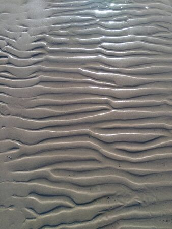 wavy lines of wet sand on the beach