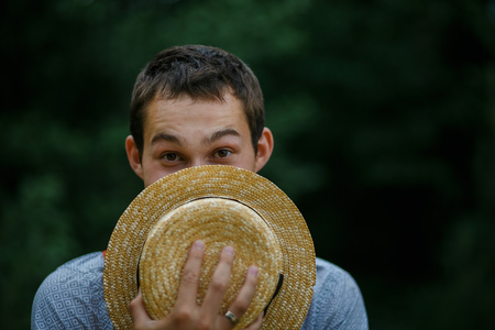 Young man hiding his face in a straw hat