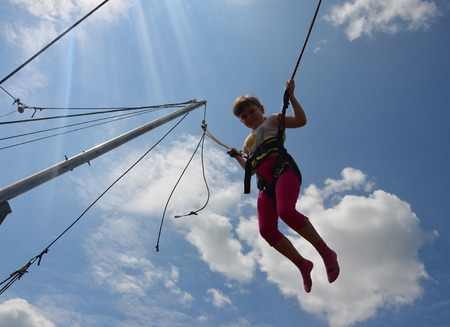 Girl jumping on a trampoline with ropes in summer in a backlight against a blue sky and white clouds