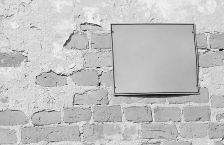 Empty information sign on old brick wall in black and white