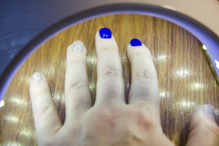 UV lamp for drying nails with gel method a manicure in the salon Stock Photo - 101647477