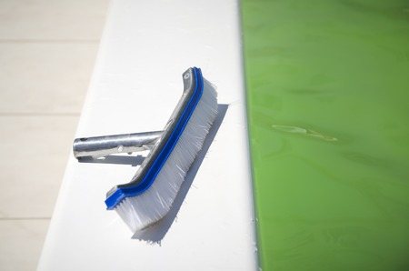 Brushing the surface of a pool to open it facing the summer season