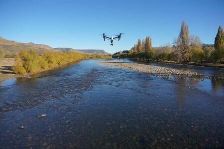 Inspire quadcopter drone flying over river. (front view)