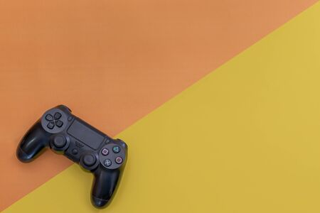 Video games black gaming controller isolated on yellow blue color background top view
