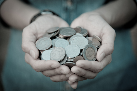 A coins in people hands in saving money concept Stock Photo