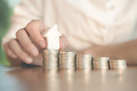 Close up pf the people hand putting the house on the row of coins in saving for buying house Stock Photo